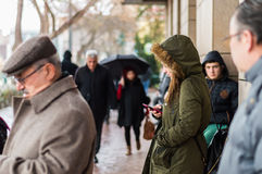 Eskisehir, Turkey - March 13, 2017: People walking in the street. On a rainy day. Young woman texting on her mobile phone while waiting Royalty Free Stock Photos