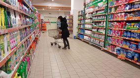 Eskisehir, Turkey - March 15, 2017: Young woman shopping in supermarket. Eskisehir, Turkey - March 15, 2017: Young brunette woman with trolley shopping in stock footage