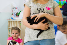 Eskisehir, Turkey - May 05, 2017: Woman holding a black kitty in her arms in a kindergarten classroom stock image