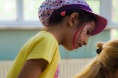 Eskisehir Turkiet - Maj 05, 2017: Förskole- liten flicka med den gula t-skjortan som poserar i klassrum Fotografering för Bildbyråer