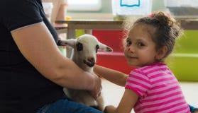 Eskisehir Turkiet - Maj 05, 2017: Lycklig liten flicka som smeker ett lamm på den djura daghändelsen i dagiset Fotografering för Bildbyråer