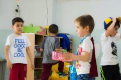 Eskisehir Turkiet - Maj 05, 2017: Söt pys med den röda kappan som bär en kopp i dagisklassrum Fotografering för Bildbyråer