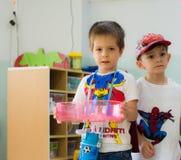 Eskisehir Turkiet - Maj 05, 2017: Söt pys med den röda kappan som bär en kopp i dagisklassrum Arkivfoto