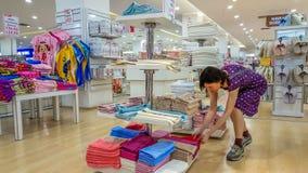 Eskisehir Turkiet - Maj 04, 2017: Undersökande handdukar för härlig brunettkvinna i ett lager i Eskisehir Royaltyfria Foton
