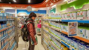 Eskisehir, Turkije - April 08, 2017: Jonge vrouw in de sectie van het babyvoedsel in een supermarkt in Eskisehir, Turkije Stock Foto's