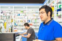 Eskisehir, Turkije - Juni 14, 2017: Portret van een jonge mannelijke apotheker die zich bij teller in apotheek bevinden stock fotografie