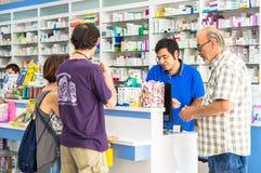 Eskisehir, Turkije - Juni 14, 2017: Positieve jonge apotheker die klanten helpen bij de teller stock afbeelding