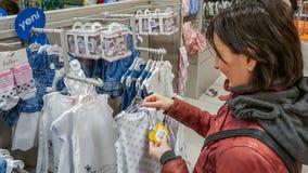Eskisehir, Turquía - 8 de abril de 2017: Compras femeninas jovenes felices del cliente en tienda de la tienda del bebé en Eskiseh Foto de archivo libre de regalías