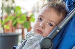 Eskisehir, Turquía - 15 de junio de 2017: El bebé soñoliento con marrón observa en el cochecito azul que mira la cámara en un caf Fotos de archivo libres de regalías
