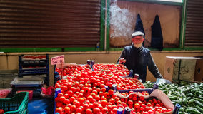 Eskisehir, Turquía - 25 de mayo de 2017: Hombre mayor con humo sobre su cabeza que vende los tomates y los pepinos en bazar local Imagenes de archivo