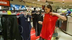 Eskisehir, Turquie - 11 août 2017 : La jeune femme regardant un habillement de sports dans des sports font des emplettes à Eskise Photo stock