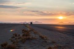 Eskortfartyg av bilkörning på en huvudväg i öknen på soluppgång royaltyfria foton