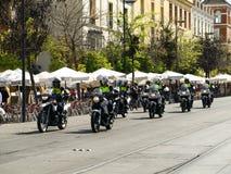 Eskortfartyg av sju polismotorcyklister som reser längs en gata i Seville, Spanien Fotografering för Bildbyråer