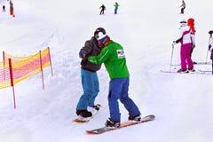 ESLOVÁQUIA, STRBSKE PLESO - 6 DE JANEIRO DE 2015: Instrutor da snowboarding de Tatra Ski School com um estudante em Strbske Pleso imagem de stock