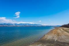 Eslováquia: Vila pequena perto da montanha de Tatra Lago Liptovska Mara no primeiro plano inverno e montanha da neve foto de stock royalty free