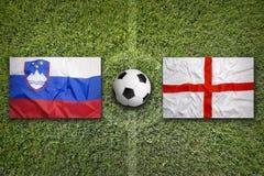 Eslovênia contra Bandeiras de Inglaterra no campo de futebol Imagens de Stock Royalty Free