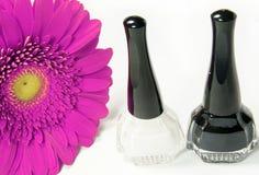 Esmalte de uñas blanco y negro y flor rosada Imagenes de archivo