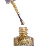 Esmalte de uñas del oro con el brillo, aislado en blanco, macro Imagen de archivo libre de regalías