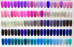 Esmalte de uñas en los clavos plásticos artificiales imagenes de archivo