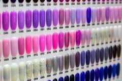 Esmalte de uñas en los clavos plásticos artificiales fotos de archivo libres de regalías
