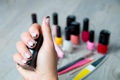 Esmalte de uñas negro en mano femenina con las herramientas para el fondo de la manicura y de la pedicura Cierre para arriba Imagenes de archivo