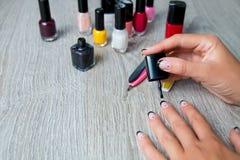 Esmalte de uñas negro que es aplicado a la mano con las herramientas para la manicura en fondo Proceso hermoso Visión superior Co Fotos de archivo
