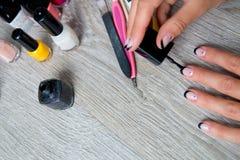 Esmalte de uñas negro que es aplicado a la mano con las herramientas para la manicura en fondo Proceso hermoso Visión superior Co Fotografía de archivo libre de regalías
