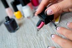 Esmalte de uñas negro que es aplicado a la mano con las herramientas para la manicura en fondo Proceso hermoso Visión superior Co Fotografía de archivo