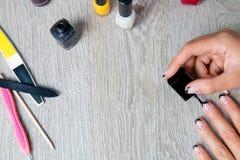 Esmalte de uñas negro que es aplicado a la mano con las herramientas para la manicura en fondo Proceso hermoso Visión superior Co Imagenes de archivo