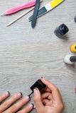 Esmalte de uñas negro que es aplicado a la mano con las herramientas para la manicura en fondo Proceso hermoso Visión superior Co Fotos de archivo libres de regalías