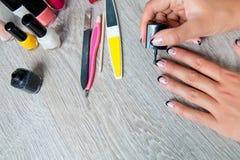 Esmalte de uñas negro que es aplicado a la mano con las herramientas para la manicura en fondo Proceso hermoso Visión superior Co Imagen de archivo libre de regalías