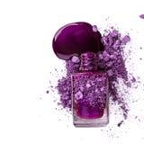 Esmalte de uñas púrpura y sombra de ojos machacada fotografía de archivo libre de regalías