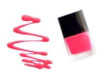 Esmalte de uñas rosado con el aislante de la salpicadura en el fondo blanco foto de archivo libre de regalías