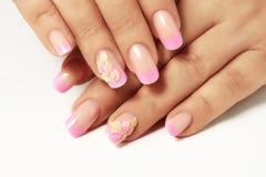 Esmalte de uñas rosado en los clavos de mujeres Fotos de archivo
