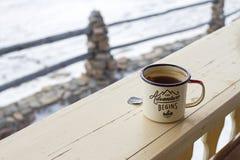 Esmalte la taza con té fuerte y la bolsita de té en una cerca de madera en un fondo natural nevoso Fotografía de archivo