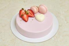 Esmalte rosado del espejo de la torta de la crema batida, adornado con los macarons y la fresa Fotografía de archivo