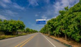 Esmeraldas,厄瓜多尔- 2016年3月16日:在海岸的被铺的路,当情报标志,围拢与abundat植被 库存照片