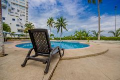 Esmeraldas, Ecuador - March 16, 2016: Beautiful swimming pool with circle form, with a rattan chair in the border in a Royalty Free Stock Photography