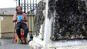 Esmola procurando do mendigo masculino idoso cego no portal da porta do cemitério filme