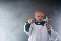 Esorcista del prete cattolico in cotta bianca e camicia nera fotografia stock