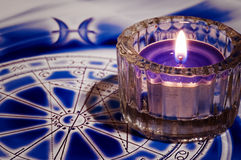 Esoteric atmoshere. Candle light over astrological background royalty free stock images