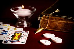 Esoteric atmosphere. Old book, runes, pendulum and tarots with candle Stock Photography