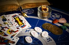 Esoteric divination. Esoteric table with astrolog wheel, magic pendulum, tarots, runes, healing stones and Iching coins Royalty Free Stock Images