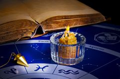 Esoteric divination. Burning candle with a magic pendulum and old book on an astrological background Stock Images
