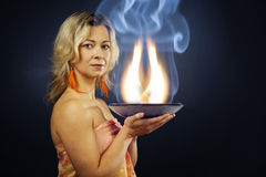 Esoteric fire. Woman of esoteric soul holding a pan full of flames describing inner flames of soul Stock Photography