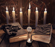 Esoteric still life with two black magic books and burning candles stock photos