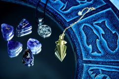 Esoteric tools. Pentagram, runes, pendulum on mirror surface with blue zodiac Royalty Free Stock Photos