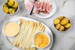 Espárrago alemán blanco del disco con el jamón cocinado y ahumado de las patatas, el Hollandaise de la salsa y la mantequilla  imagen de archivo