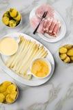 Espárrago alemán blanco del disco con el jamón cocinado y ahumado de las patatas, el Hollandaise de la salsa y la mantequilla  fotos de archivo