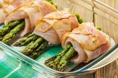 Espárrago envuelto en pollo y tocino en un plato de la hornada Foto de archivo